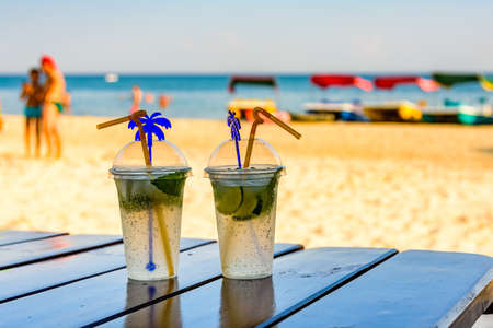 Two mojito cocktails on wooden table with sandy beach on background