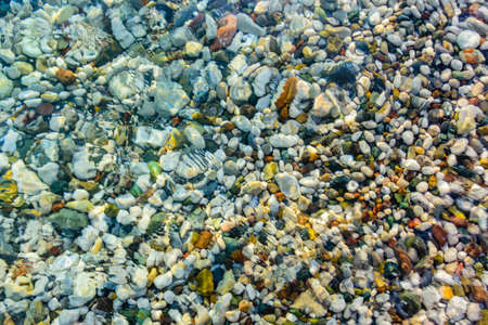 Texture of pebbles under water at seaside. Natural background Banco de Imagens