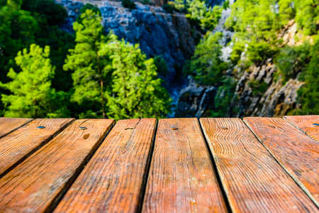 Empty wooden table. Deep canyon on background