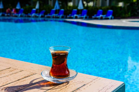 Black tea in traditional turkish glass on table near swimming pool