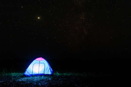 Tourist tent at night. Night sky with many stars