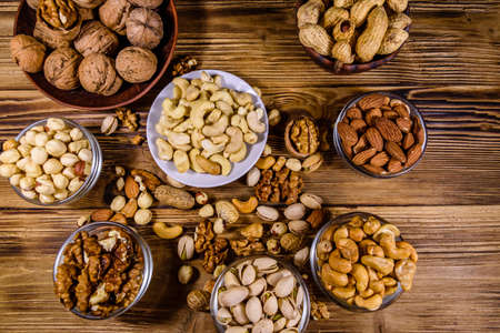 Various nuts (almond, cashew, hazelnut, pistachio, walnut) in bowls on wooden table. Vegetarian meal. Healthy eating concept. Top view
