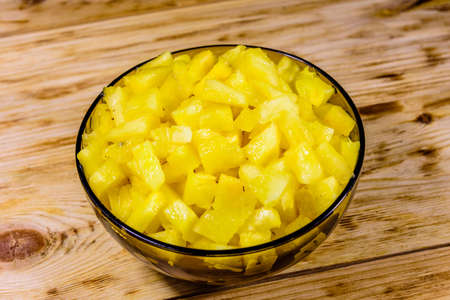 Glass bowl with chopped pineapple on rustic wooden table Stock fotó