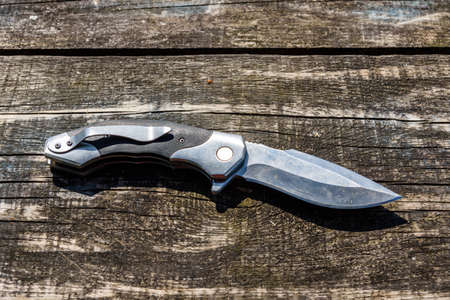 Survival folding knife on rustic wooden background