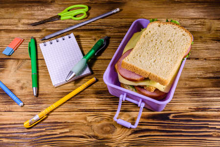 Different stationeries and lunch box with sandwiches on wooden table