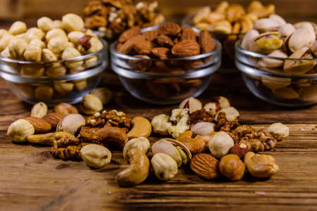 Various nuts (almond, cashew, hazelnut, pistachio, walnut) in glass bowls on wooden table. Vegetarian meal. Healthy eating concept Stock fotó