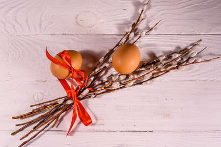 Pussywillow bouquet and easter eggs on white wooden table. Top view