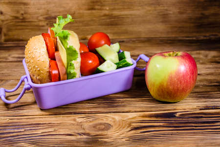 Ripe apple and lunch box with hamburger, cucumbers and tomatoes on rustic wooden table Stock fotó