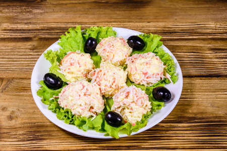 White plate with crab-cheese balls, black olives and lettuce leaves on rustic wooden table Stock fotó