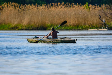 Young man kayaking on river at summer
