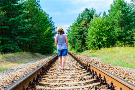 Lonely young woman on railway in forest Stock fotó