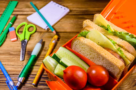 Different stationeries and lunch box with sandwiches, cucumbers and tomatoes on rustic wooden table