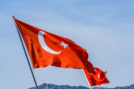 Red turkish flag with crescent and star waving against sky