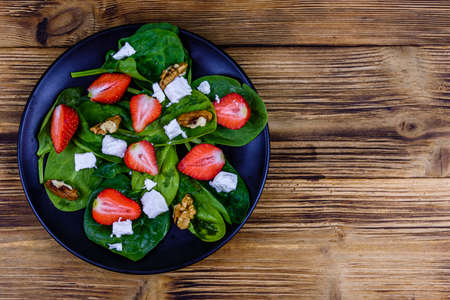 Salad with spinach leaves, feta cheese, walnuts and strawberry on black plate. Top view