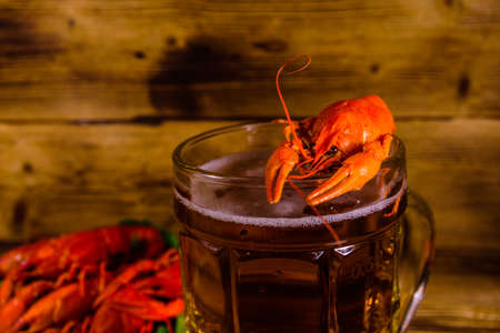 Glass of beer and boiled crayfish on rustic wooden table