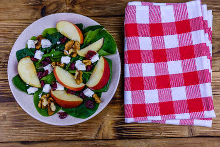Salad with spinach leaves, feta cheese, cranberries, walnuts and apple in ceramic plate. Top view Stock fotó