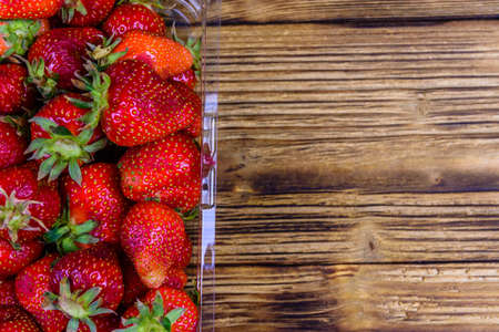 Plastic container with pile of ripe strawberries on rustic wooden table. Top view