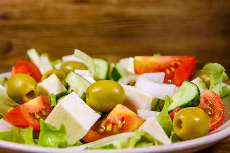 Ceramic plate with greek salad on rustic wooden table Stock fotó
