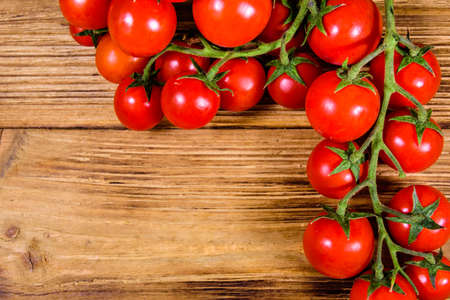 Heap of small cherry tomatoes on rustic wooden table. Top view Stock fotó