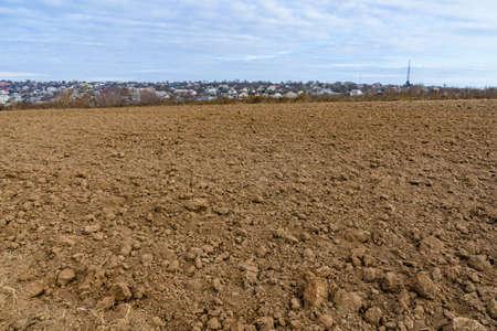 Plowed field at autumn. City Uman on background. Ukraine