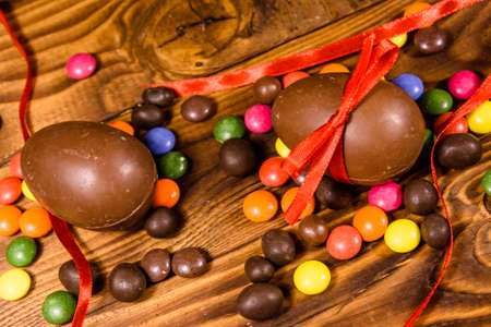 Chocolate easter eggs and multicolored candies on rustic wooden table