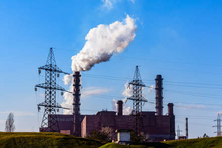 View on smoke pipes of factory against blue sky. Environmental pollution Stockfoto