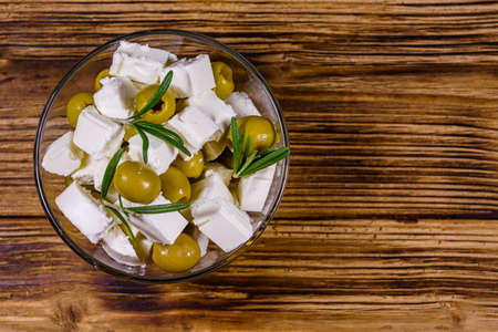 Chopped feta cheese, rosemary and olives in glass bowl on wooden table. Top view Stockfoto