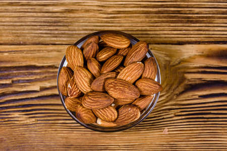Glass bowl with peeled almond nuts on wooden table. Top view