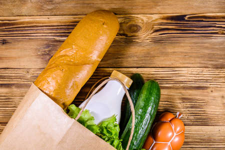 Paper bag with different food from grocery on wooden table. Supermarket shopping concept. Top view