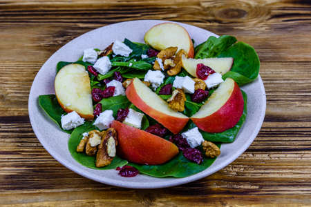 Salad with spinach leaves, feta cheese, cranberries, walnuts and apple in ceramic plate