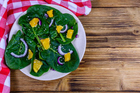Salad with spinach leaves, pieces of orange, sesame seeds and onion in ceramic plate