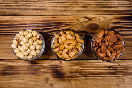 Various nuts (almond, cashew, hazelnut) in glass bowls on wooden table. Vegetarian meal. Healthy eating concept. Top view