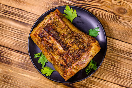 Baked piece of pork belly and parsley on black plate