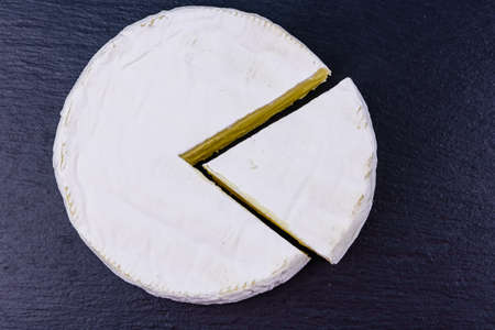 Piece of brie cheese on slate board. Top view