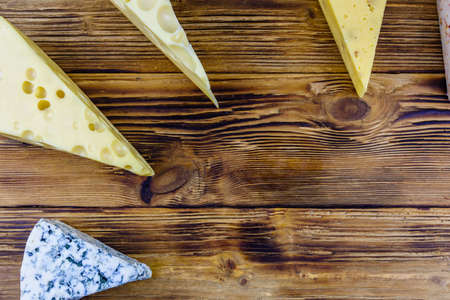 Various types of cheese on wooden background. Top view