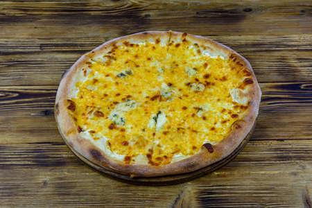 Pizza quattro formaggi (four cheeses) on wooden background Stockfoto