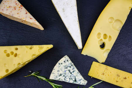 Various types of cheese on slate board. Top view