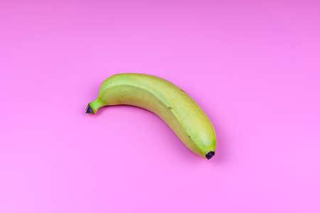 Whole yellow banana isolated on pink background