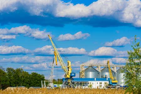 Tall construction cranes near grain storage bins