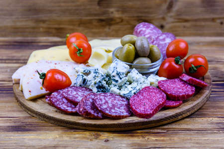 Slices of various types of cheese and dry smoked salami sausage on a wooden background. Traditional italian antipasto platter