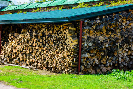 Pile of stacked firewood at yard, prepared for heating house
