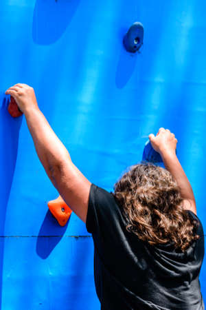 Young woman exercising at blue climbing wall
