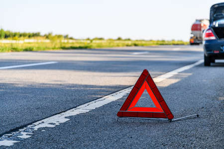 Broken car at roadside. Red warning triangle at foreground Stockfoto