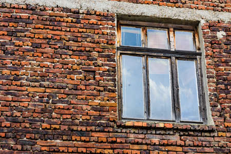 Window in red brick wall of ancient residential building