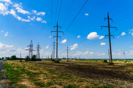 High voltage power line at field on summer