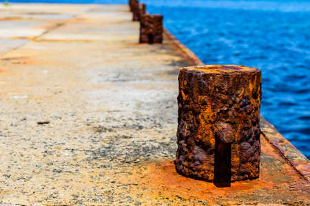 Old rusty mooring bollard at the pier