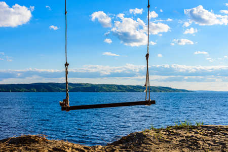Empty swing hanging from tree at bank of river Dnieper