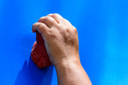 Young woman hand holding hook at blue climbing wall