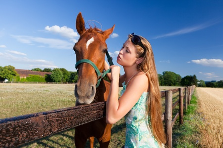 horse and blond girl in paddock on summers day photo
