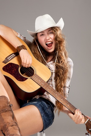 Sesy cowgirl in cowboy hat with acoustic guitar photo